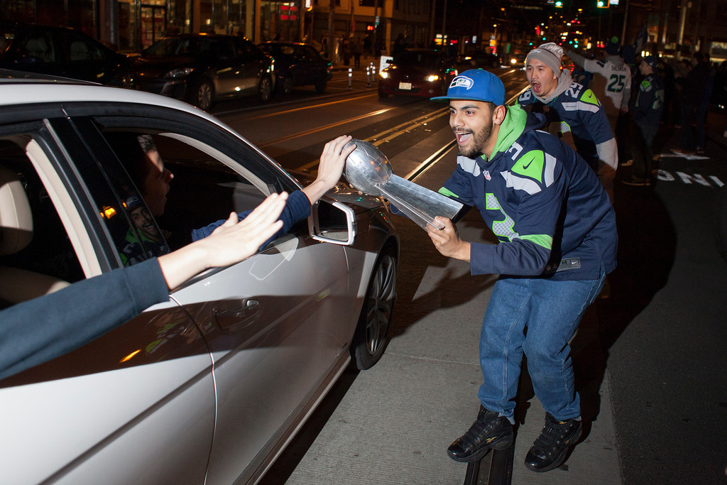 . Seattle Seahawks fans celebrate with a replica Vince Lombardi Trophy after watching their team win the Super Bowl on February 2, 2014 in Seattle, Washington. The Seahawks defeated the Denver Broncos 43-8 in Super Bowl XLVIII.  (Photo by David Ryder/Getty Images)