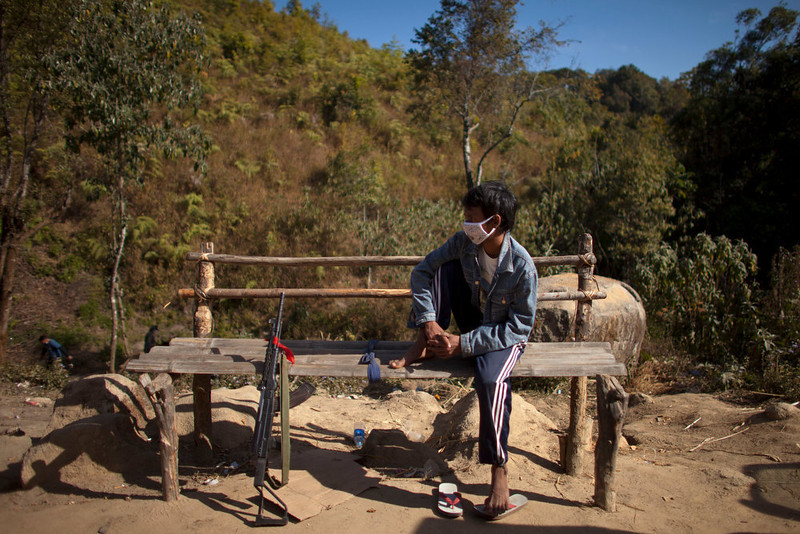 . A man rests with a rifle at a roadside checking post near Ma Ja Yang in Kachin state, Myanmar, Monday, Jan. 28, 2013. (AP Photo/Alexander F. Yuan)