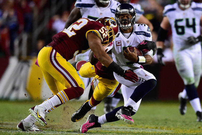 . Quarterback Russell Wilson #3 of the Seattle Seahawks takes a hit from inside linebacker Keenan Robinson #52 of the Washington Redskins in the second half of a game at FedExField on October 6, 2014 in Landover, Maryland.  (Photo by Patrick Smith/Getty Images)