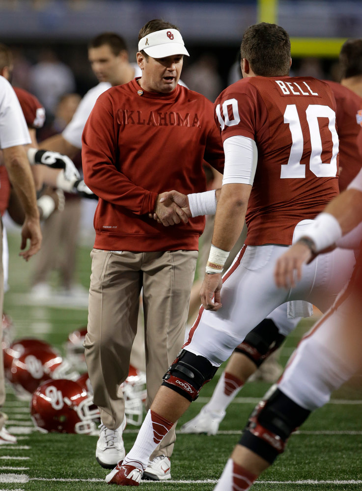 Description of . Oklahoma coach Bob Stoops shakes hands with quarterback Blake Bell (10) as the team stretches before the Cotton Bowl NCAA college football game against Texas A&M on Friday, Jan. 4, 2013, in Arlington, Texas. (AP Photo/Tony Gutierrez)