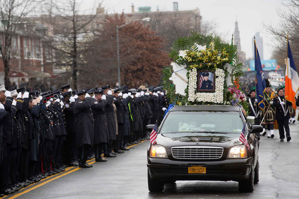 . CORRECTS VEHICLE IS NOT A HEARSE  - The vehicle leading the funeral procession of New York Police Department Officer Wenjian Liu, seen in photo, passes along the funeral route as police officers salute, Sunday, Jan. 4, 2015, in the Brooklyn borough of New York. Liu and his partner, officer Rafael Ramos, were killed Dec. 20 as they sat in their patrol car on a Brooklyn street. The shooter, Ismaaiyl Brinsley, later killed himself. (AP Photo/John Minchillo)