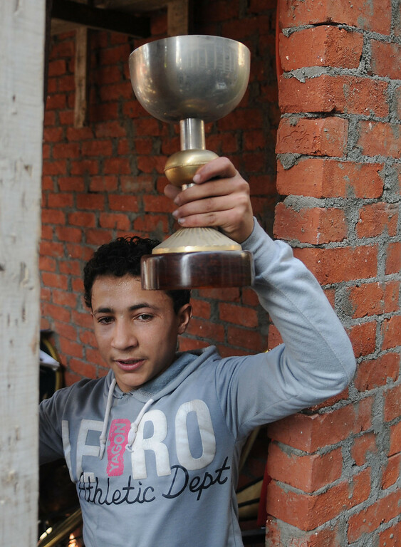. A young boy displays a soccer trophy cup, one of many looted mementoes of the Egyptian national team, that were either stolen or burned in violence following a court ruling in Cairo, Egypt, Saturday, March 9, 2013. (AP Photo/Mohammed Asad)