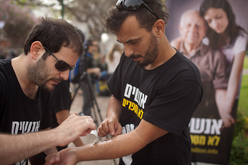 Description of . A young Israeli sticks a temporary tattoo of prisoner numbers on his arm, as part of a Holocaust remembrance campaign on April 8, 2013 in Rishon Lezion, Israel. The temporary tattoos replicate the numbers tattooed onto the arms of the prisoners at the Auschwitz-Birkenau camp and allow the wearer to connect with a disappearing generation of survivors. (Photo by Uriel Sinai/Getty Images)