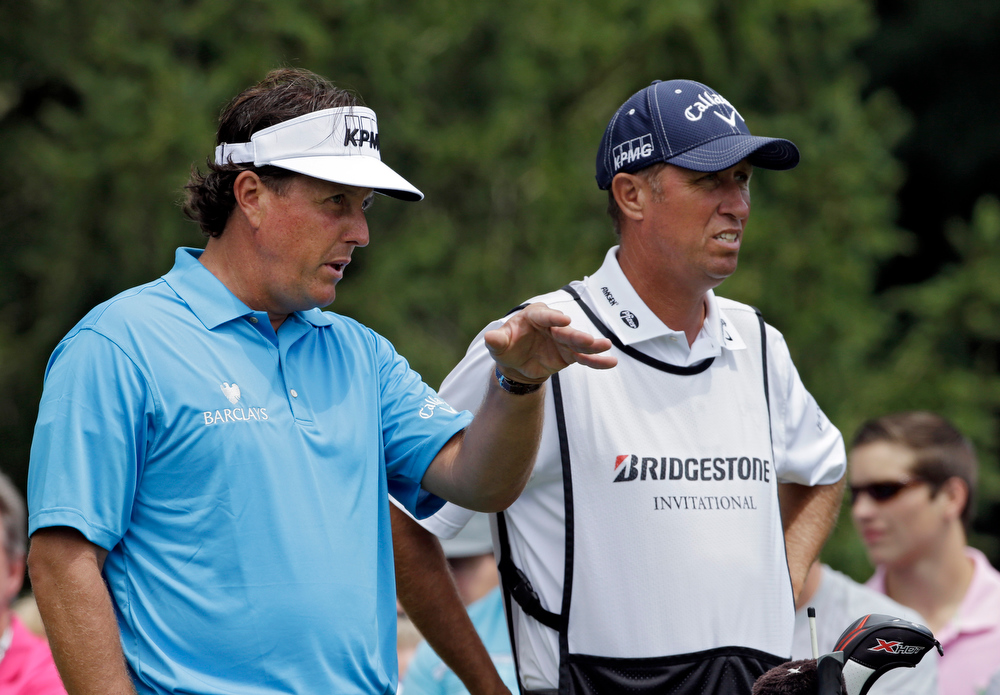 . Phil Mickelson, left, talks with his caddie Jim Mackay on the fourth tee during the final round of the Bridgestone Invitational golf tournament Sunday, Aug. 4, 2013 at Firestone Country Club in Akron, Ohio. (AP Photo/Mark Duncan)