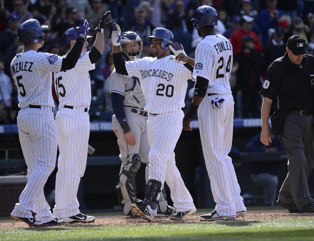 . Colorado Rockies Wilin Rosario (20) is congratulated by Carlos Gonzalez (5) Jordan Pacheco (15) and Dexter Fowler (24) after his three run home run in the 7th inning against the San Diego Padres April 7, 2013 at Coors Field. (Photo By John Leyba/The Denver Post)