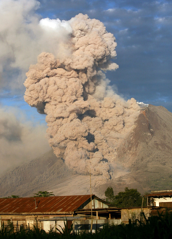 . Mount Sinabung releases pyroclastic flows during an eruption as seen from Perteguhan, North Sumatra, Indonesia, Monday, Jan. 6, 2014. The 2,600-meter (8,530-foot) volcano has sporadically erupted since September. Authorities extended a danger zone around a rumbling volcano in western Indonesia on Sunday after it spewed blistering gas farther than expected, sending panicked residents streaming down the sides of the mountain. (AP Photo/Binsar Bakkara)