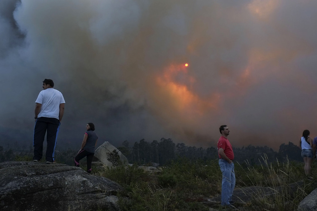 . People watch smoke rise into the air at the site of a wildfire in Lousame, near A Coruna, on August 29, 2013. Spain is prone to forest fires in summer because of soaring temperatures, strong winds and dry vegetation. Last year wildfires destroyed some 150,000 hectares of land in Spain from January to July, after one of the driest winters on record.   PEDRO ARMESTRE/AFP/Getty Images