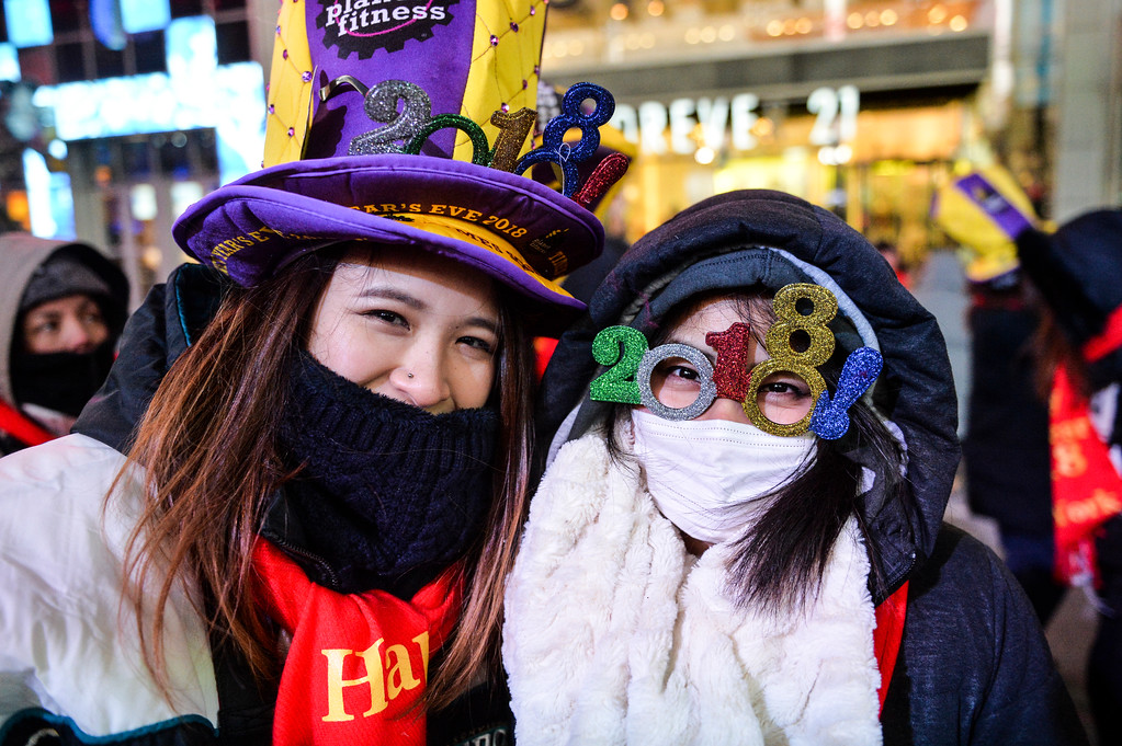 . Niina Hijikata, right, and Tomomi Waraya, left, both from Japan, wear 2018 glasses as they pose for a photo in Times Square during a New Year\'s Eve celebration, Sunday, Dec. 31, 2017, in New York. (AP Photo/Go Nakamura)