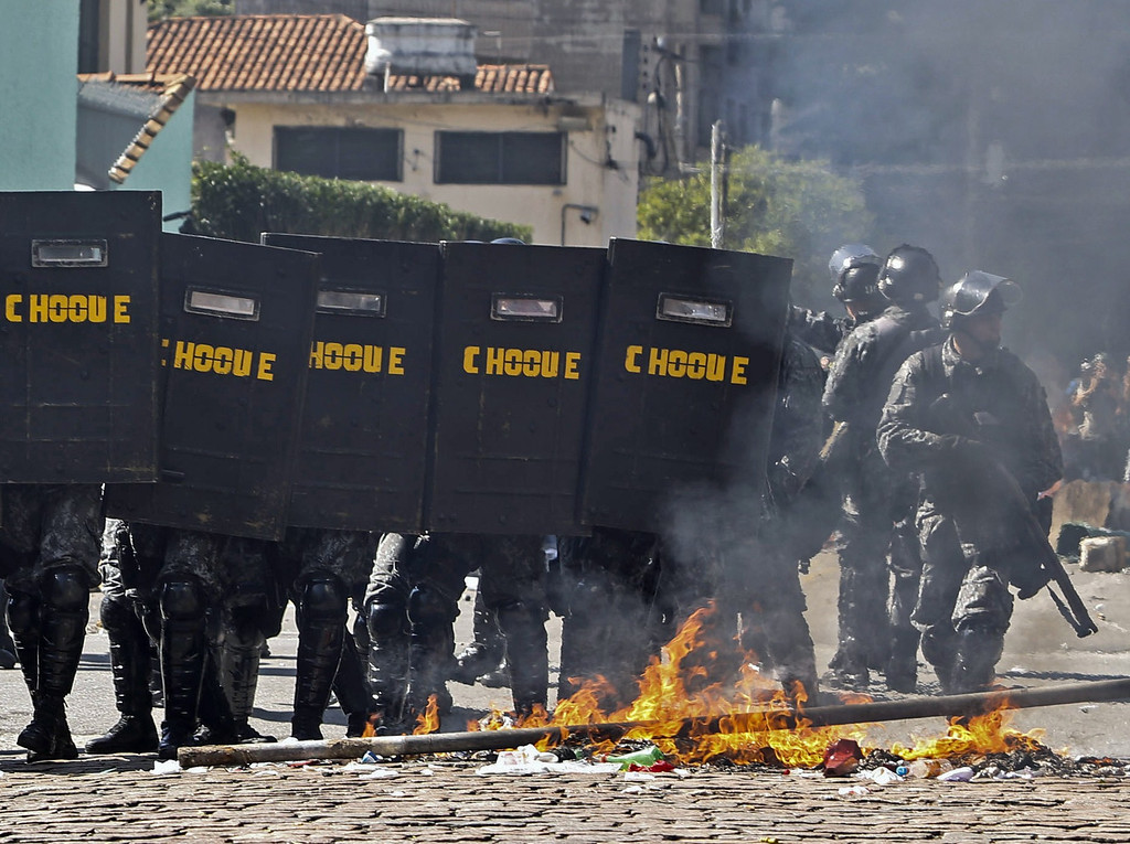 . Riot policemen move by a fire set up by demonstrators during an anti-World Cup protest on the morning the Brazilian mega-city hosts the tournament\'s opening match, in Sao Paulo on June 12, 2014.   AFP PHOTO / Miguel Schincariol/AFP/Getty Images