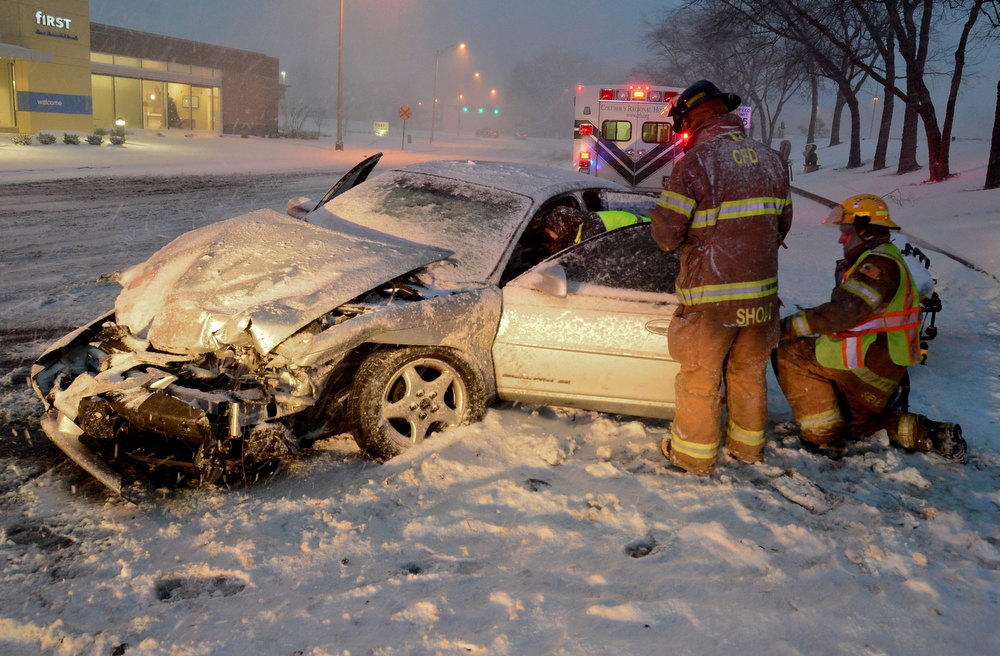 Description of . Rescuers work to move a driver injured in a wreck on a slick, snow-covered street in Columbus, Ind., Wednesday, Dec. 26, 2012. The blizzard warning issued the day before by National Weather Service came to fruition in the region Wednesday as winds picked up and snow began falling in earnest before dawn. (AP Photo/The Republic, Joe Harpring)
