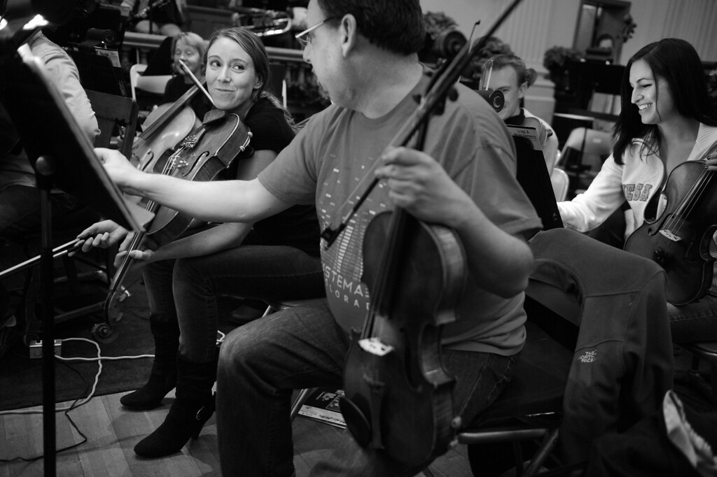 """. Violist Elizabeth O\'Brien, shares a laugh with section principal William Hinkie III, during the Denver Philharmonic Orchestra rehearsal at the KPOF Concert Hall in Denver, CO, Wednesday November 28, 2012. O\'Brien started playing the piano at age 5 then picked up the viola in the 5th grade. \""""In 5th grade it\'s pretty horrendous,� she said. �But, once you get past that, the music you make is really pretty.\""""  Outside the Orchestra O\'Brien, 26, is a clinical pharmacist. She said she never pursued music as a profession, \""""It\'s my passion. I didn\'t want it to be my career. I wanted it to be something I always enjoyed.\""""  O\'Brien is in her second season with the orchestra. �I think in any orchestra the violas have more fun than anyone. William (Hinkie) is an extraordinary musician. But he\'s also so much fun. You can\'t help but have fun when you sit next to him.\"""" Craig F. Walker, The Denver Post"""