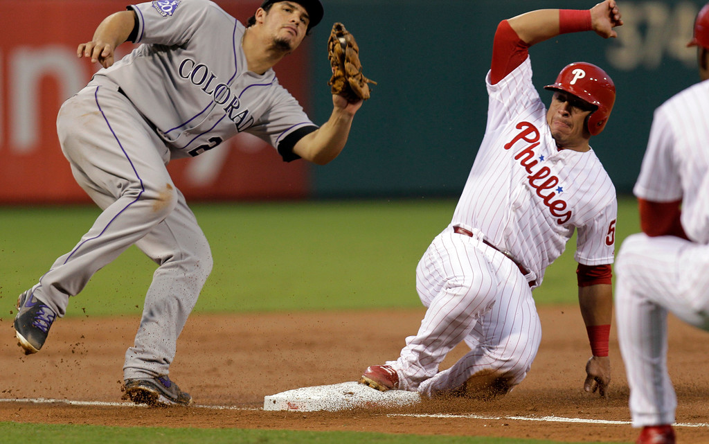 . Philadelphia Phillies\' Carlos Ruiz is safe on third on a hit by Cody Asche bringing in Domonic Brown for the run before Colorado Rockies third baseman Nolan Arenado can make the tag in the second inning in a baseball game, Thursday, Aug. 22, 2013, in Philadelphia. (AP Photo/Laurence Kesterson)