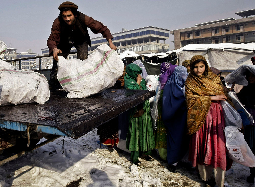 Description of . Afghan displaced women stand in line to receive fire wood provided by a German run charity organization at a refugee camp in Kabul, Afghanistan, Tuesday, Dec. 18, 2012. A German run charity organization, known as Johanniter, distributed winter relief assistance to some 279 internally displaced families in Kabul. (AP Photo/Musadeq Sadeq)