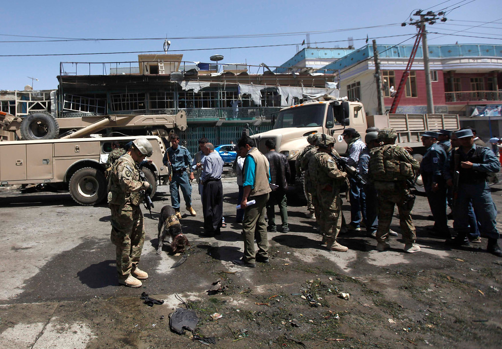 . NATO soldiers with the International Security Assistance Force (ISAF) investigate at the site of a suicide attack in Kabul May 16, 2013. REUTERS/Mohammad Ismail