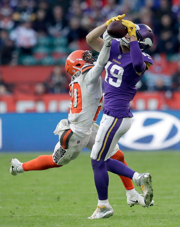 . Minnesota Vikings wide receiver Adam Thielen, right, catches the ball despite the challenge of Cleveland Browns safety Briean Boddy-Calhoun (20) during the second half of an NFL football game at Twickenham Stadium in London, Sunday Oct. 29, 2017. (AP Photo/Tim Ireland)