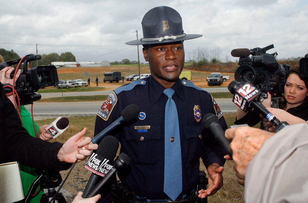 Description of . Alabama State Trooper Charles Dysert speaks to the media near the scene of a shooting and hostage taking in Midland City, Alabama, January 30, 2013. A gunman boarded an Alabama school bus ferrying children home from school on Tuesday and fatally shot the driver before fleeing with a young child and holing up in an underground bunker, Alabama media reported. Sheriff\'s officials confirmed that one person had been killed in a shooting involving a school bus in Alabama\'s Dale County but gave scant details other than to say that a child was present at the scene in Midland City. REUTERS/Phil Sears