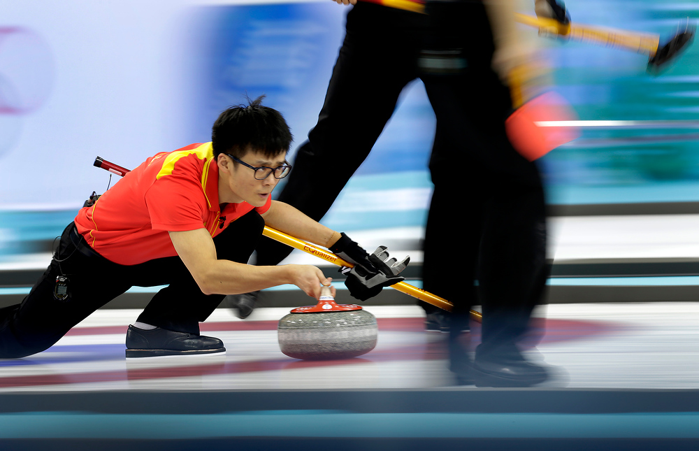 . China\'s Zang Jialiang delivers the rock during the men\'s curling bronze medal game against Sweden at the 2014 Winter Olympics Friday, Feb. 21, 2014, in Sochi, Russia. (AP Photo/Wong Maye-E)