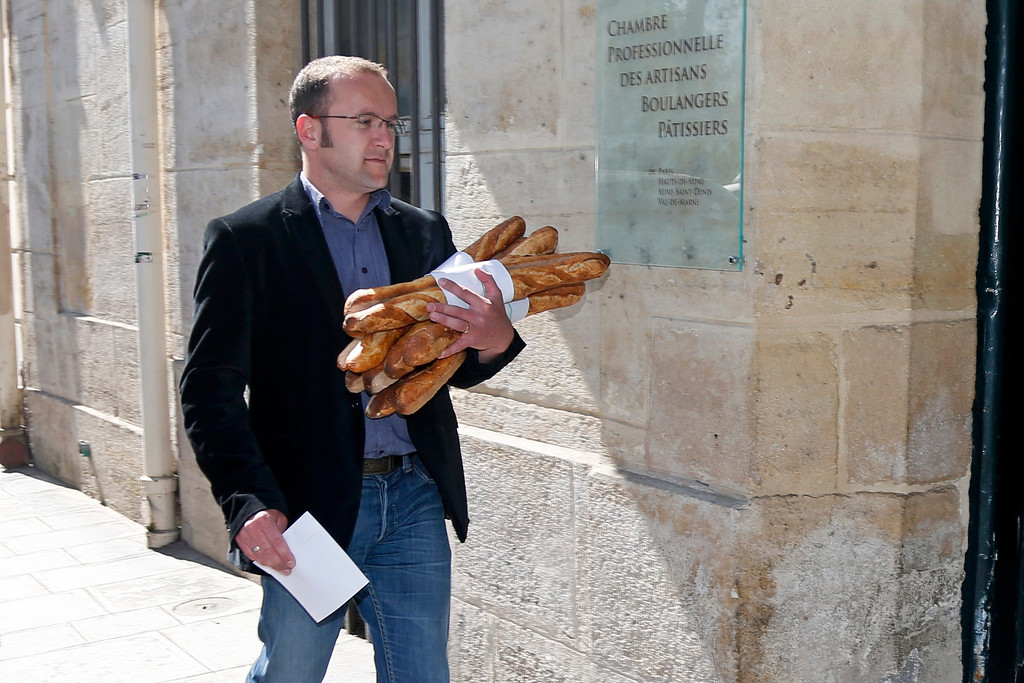 . A baker carries an armful of baguettes, French bread, as he arrives to compete for the \'Grand Prix de la Baguette de la Ville de Paris\' (Best Baguette of Paris 2013) annual prize at the Chambre Professionnelle des Artisans Boulangers Patissiers in Paris April 25, 2013. The baguette is a French cultural symbol par excellence and the competition saw 203 Parisian bakers who compete for recognition as finest purveyor of one of France\'s most iconic staples. The baguettes are registered, given anonymous white wrappings and an identification number. They are then carefully weighed and measured to ensure they do not violate the contest\'s strict rules. 52 entries were withdrawn for failing to measure between 55-70cm long or not matching the acceptable weight of between 250-300g. Every year, the winner earns the privilege of baking bread for the French President.   REUTERS/Charles Platiau