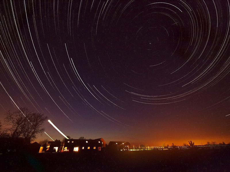 Made a few nationals with this one. Volcanic ash still carpeting the UK and most of EU from the fallout and eruption of Eyjafjallajokull in Iceland. Flights continue to be grounded across the entire UK. Not all bad news ;-) Good opportunity for clutter free star trails. Captured on the evening/early hours of April 16/17th. 7 hrs of continuous 15s exposures, stacked. Note the purply tone and swollen light pollution, all compounded by the volcanic ash. Also a meteor top right :-) Captured with Olympus E3, 7-14mm SWD lens.