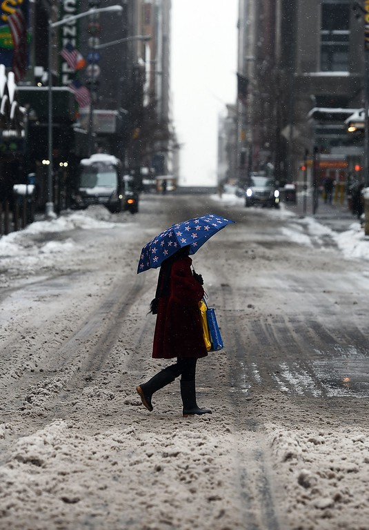 . A woman walks on a nearly deserted street in New York\'s Times Square what is normally a crowed morning rush hour after a snowstorm on January 27, 2015. A blizzard initially billed as possibly one of the worst ever in New York left only moderate snow in the Big Apple -- and officials and forecasters red-faced -- as New England bore the brunt of the storm on January 27. Travel bans were lifted and limited public transport resumed in New York, where officials were forced to launch a vigorous defense of the measures put in place as Winter Storm Juno moved in on Monday. AFP PHOTO/JEWEL SAMAD/AFP/Getty Images