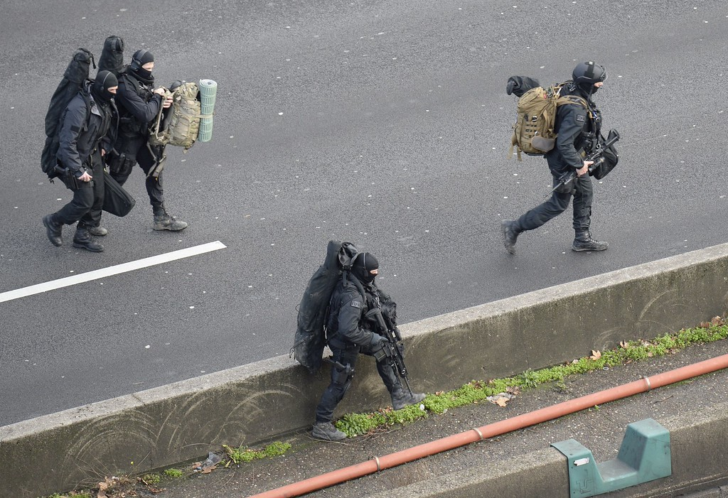 """. Members of the French police special force RAID walk with their equipment on the \""""peripherique\"""" (circular road) in Saint-Mande, near Porte de Vincennes, eastern Paris, on January 9, 2015 to take their positions after at least one person was injured when a gunman opened fire at a kosher grocery store on January 9, 2015 and took at least five people hostage, sources told AFP. The attacker was suspected of being the same gunman who killed a policewoman in a shooting in Montrouge in southern Paris on January 8.  AFP PHOTO / ERIC  FEFERBERG/AFP/Getty Images"""