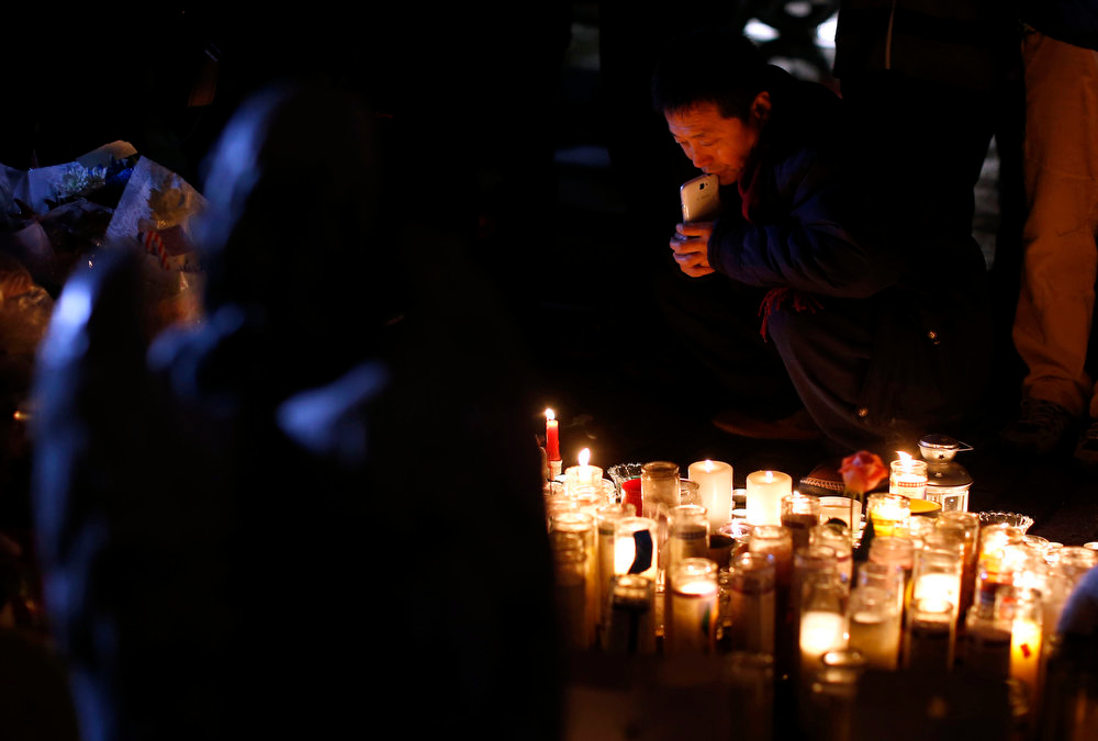 Description of . An angel statue stands over a memorial to shooting victims as a man gazes at the candles placed there, Monday, Dec. 17, 2012, in Newtown, Conn.  A gunman walked into Sandy Hook Elementary School in Newtown Friday and opened fire, killing 26 people, including 20 children. (AP Photo/Jason DeCrow)