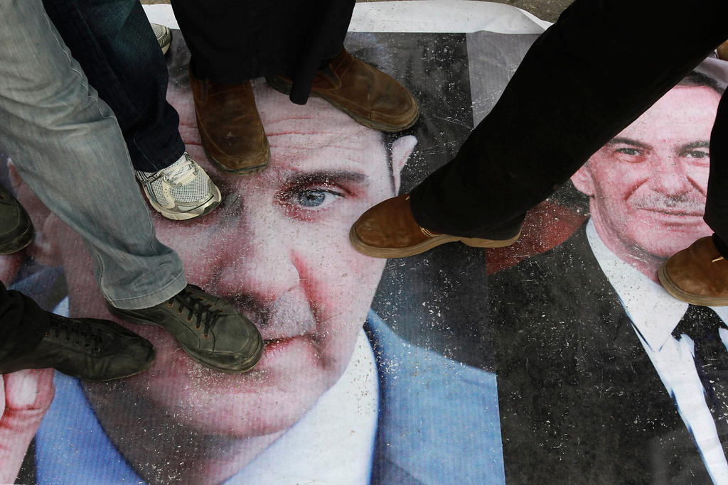 . Syrians living in Jordan step on a picture of Syria\'s President Bashar al-Assad and his father Syria\'s late president Hafez al-Assad during a protest marking two years since the start of the uprising, in front of the Syrian embassy in Amman March 15, 2013. REUTERS/Muhammad Hamed