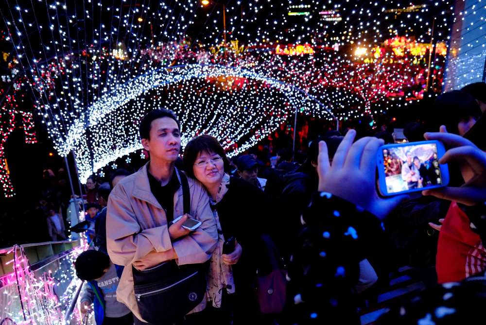 Description of . A couple pose for a photograph in an illuminated stairwell during the Lantern Festival that marks the end to the Chinese lunar New Year celebrations, in Taipei, Taiwan, Sunday, Feb. 24, 2013. (AP Photo/Wally Santana)