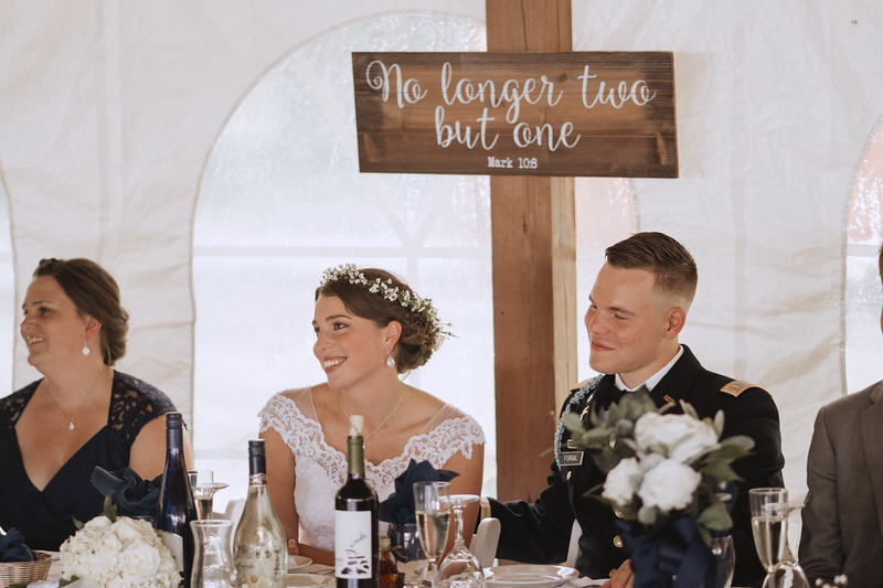"Bride and groom sitting at the head table during a wedding reception, smiling as they listen to a speech. A painted sign above them reads, ""no longer two but one Mark 10:8"""
