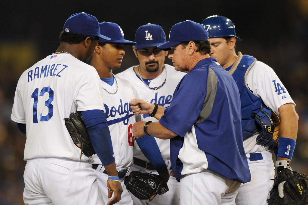 . Dodger pitching coach Rick Honeycutt talks to reliever Jose Dominguez, second from left, after Dominquez walked two batters against the Rockies, Friday, July 12, 2013, at Dodger Stadium. (Michael Owen Baker/Staff Photographer)
