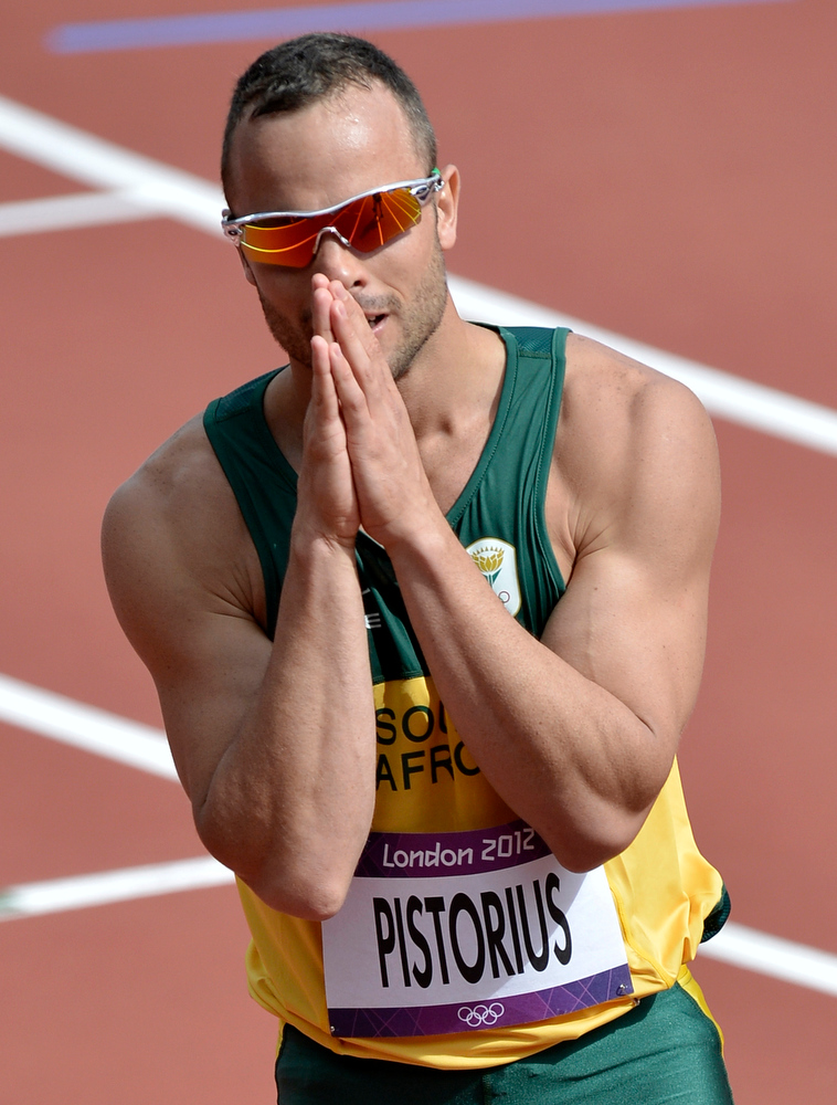 Description of . This is a Saturday, Aug. 4, 2012 file photo of South Africa's Oscar Pistorius  as he reacts after finishing first in a men's 400-meter heat during the athletics in the Olympic Stadium at the 2012 Summer Olympics, London  Paralympic superstar Oscar Pistorius was charged Thursday Feb. 14. 2013 with the murder of his girlfriend who was shot inside his home in South Africa, a stunning development in the life of a national hero known as the Blade Runner for his high-tech artificial legs. (AP Photo/Martin Meissner, File)