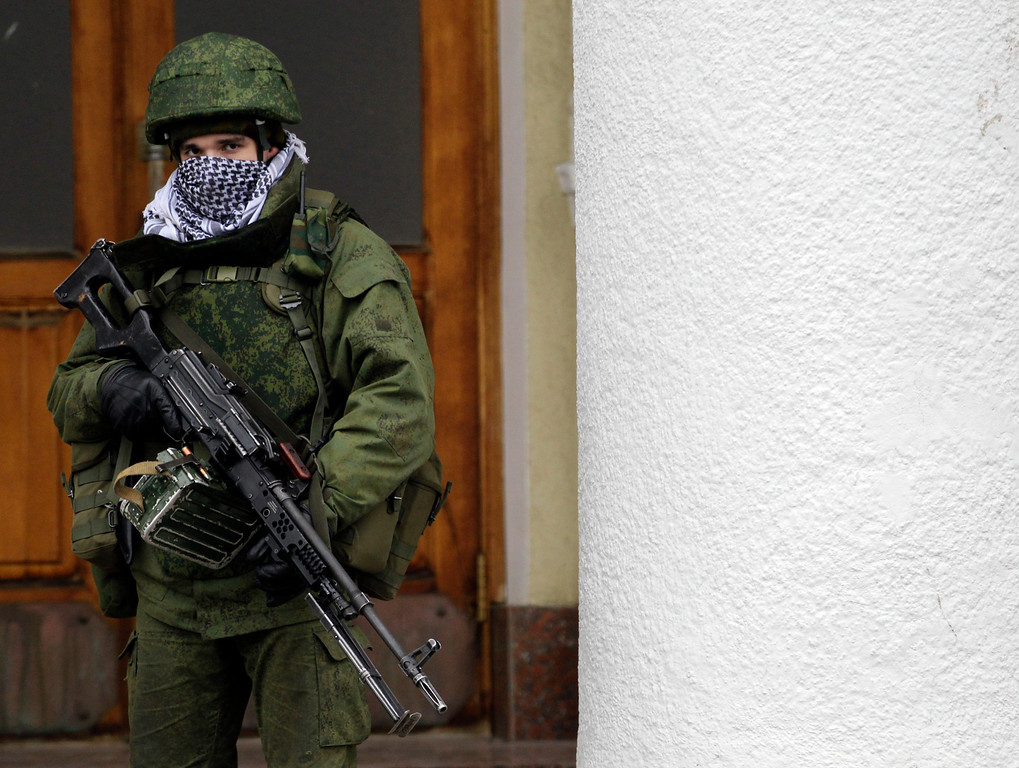 . An unidentified armed man patrols in front of the airport in Simferopol, Ukraine, Friday, Feb. 28, 2014. Russian troops took control of the two main airports in the strategic peninsula of Crimea, Ukraine\'s interior minister charged Friday, as the country asked the U.N. Security Council to intervene in the escalating conflict. Russian state media said Russian forces in Crimea denied involvement. No violence was reported at the civilian airport in Crimea\'s capital of Simferopol or at the military airport in the Black Sea port of Sevastopol, also part of Crimea. At the Simferopol airport, a man claiming to speak for the camouflage-clad forces patrolling the airport described them as Crimean militiamen.  (AP Photo/Darko Vojinovic)