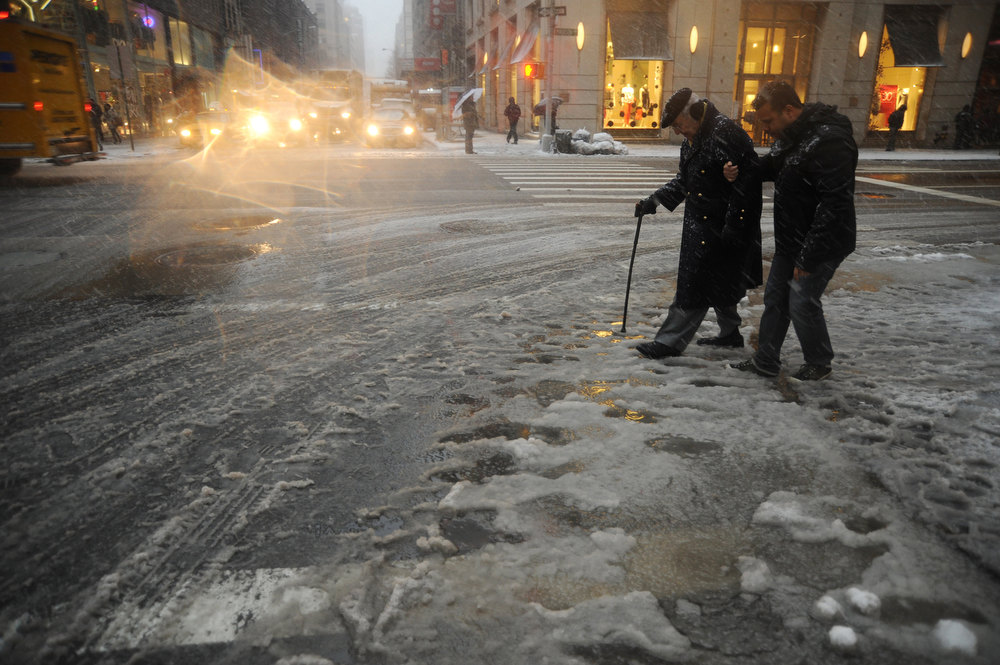 ". New York City residents cross a street covered in slush on February 8, 2013 during a storm affecting the northeast US. The storm was forecast to bring the heaviest snow to the densely-populated northeast corridor so far this winter, threatening power and transport links for tens of millions of people and the major cities of Boston and New York. New York and other regional airports saw more than 4,500 cancellations ahead of what the National Weather Service called ""a major winter storm with blizzard conditions\"" along most of the region\'s coastline. MEHDI TAAMALLAH/AFP/Getty Images"