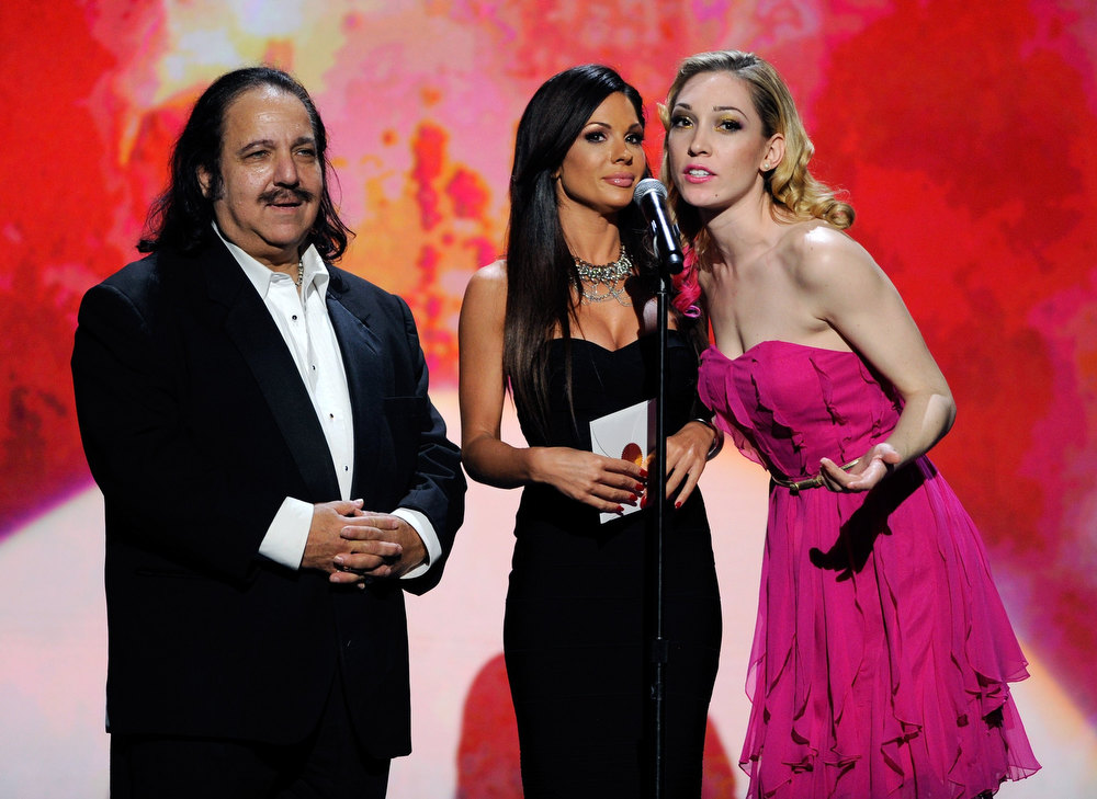 Description of . (L-R) Adult film actor Ron Jeremy and adult film actresses Kirsten Price and Lily LaBeau present an award during the 29th annual Adult Video News Awards Show at The Joint inside the Hard Rock Hotel & Casino January 21, 2012 in Las Vegas, Nevada.  (Photo by Ethan Miller/Getty Images)