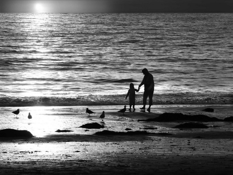Mother and daughter at sunset on the California coast