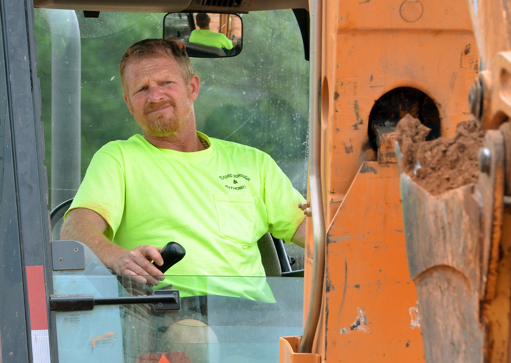 . Telford Borough municipal employee Rob Ruth keeps his eye on the bucket as he uses a backhoe to dig a trench for  installation of drainage system components for the the new basketball courts, part of the upgrades being done to the park next to the Indian Valley Library.   Monday, July 21, 2014.   Photo by Geoff Patton