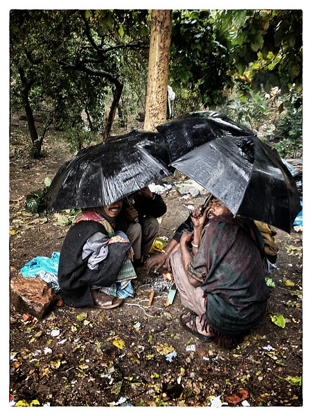 Delhi, India, Feb 2013 -    Group of men take shelter under umbrellas in a  makeshift slum in south delhi an area where top 5 star hotels - The Lodhi  and The Oberoi Hotels are located.   Images for the Global Post's special report -   The Great Divide:  Global income inequality and its cost    Photograph:  Sami SIVA