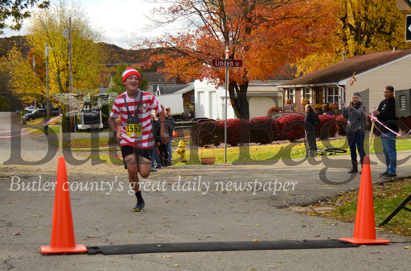 Joseph Harmanos, 14, of Evans City, crosses the finish line Sunday in the 5K run at the 10th Annual Great Pumpkin Race in Zelienople. Alex J. Weidenhof/Butler Eagle