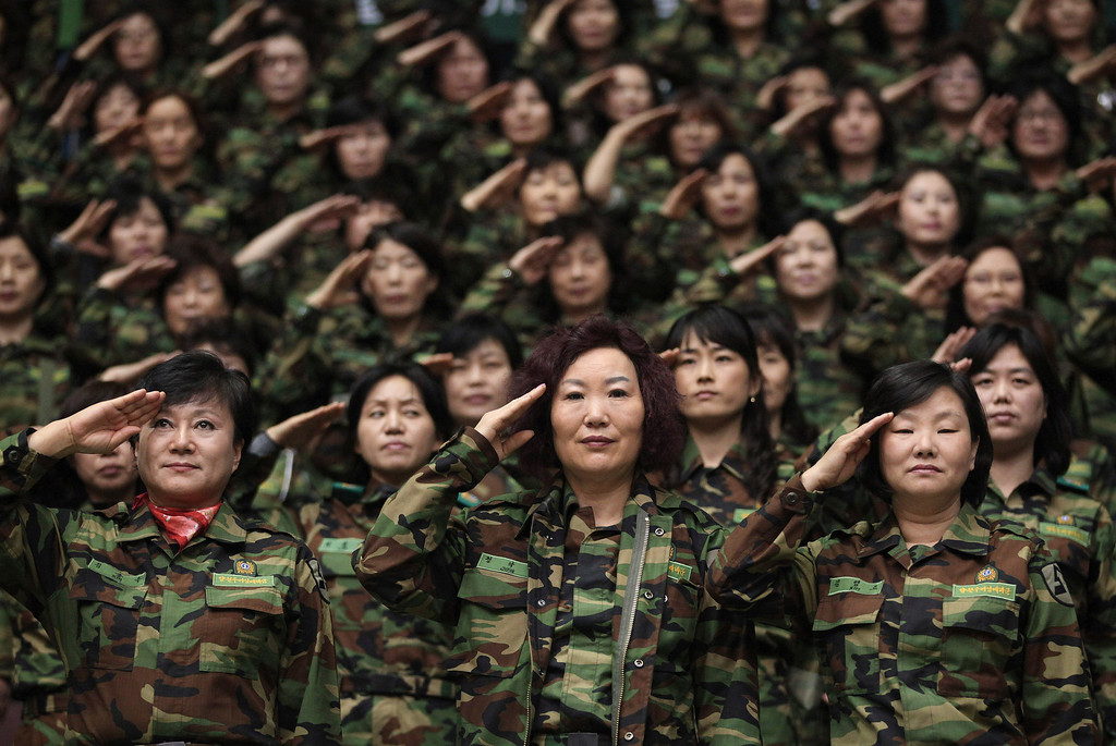 . South Korean army reservists salute during their Foundation Day ceremony at a gymnasium in Seoul, South Korea, Friday, April 5, 2013. About 1,000 reservists gathered here to denounce North Korean for their escalating threat for war. North Korea has been railing against U.S.-South Korean military exercises that began in March and are to continue until the end of this month. The allies insist the exercises in South Korea are routine, but the North calls them rehearsals for an invasion and says it needs nuclear weapons to defend itself. (AP Photo/Ahn Young-joon)