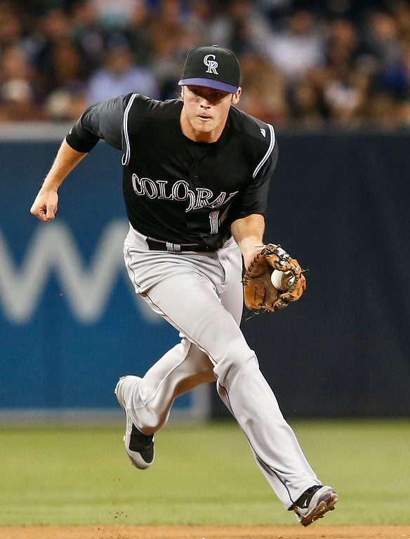 . Colorado Rockies shortstop Josh Rutledge goes behind second base to field a bouncer hit by San Diego Padres\' Abraham Almonte in the seventh inning of a baseball game Tuesday, Aug. 12, 2014, in San Diego. Rutledge threw out Almonte at first. (AP Photo/Lenny Ignelzi)