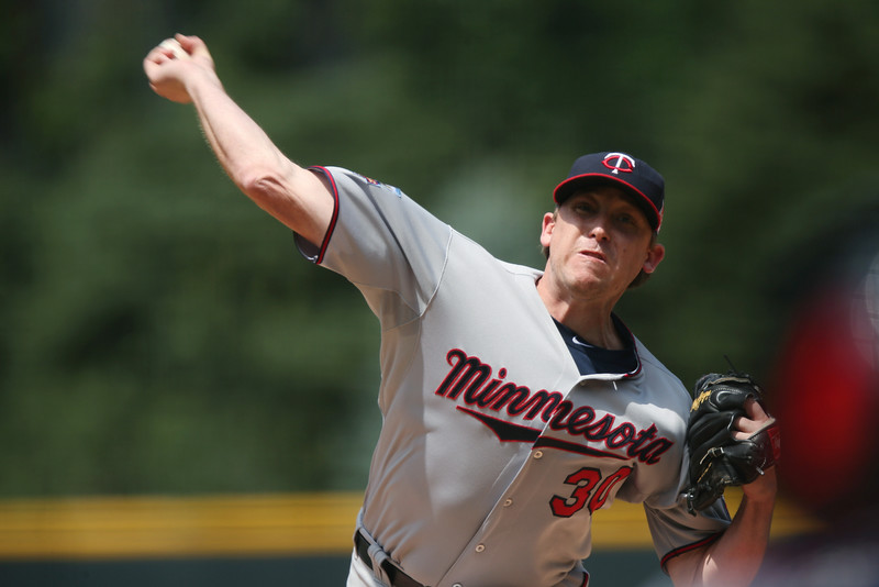 . Minnesota Twins starting pitcher Kevin Correia works against the Colorado Rockies in the first inning of an interleague baseball game in Denver on Saturday, July 12, 2014. (AP Photo/David Zalubowski)