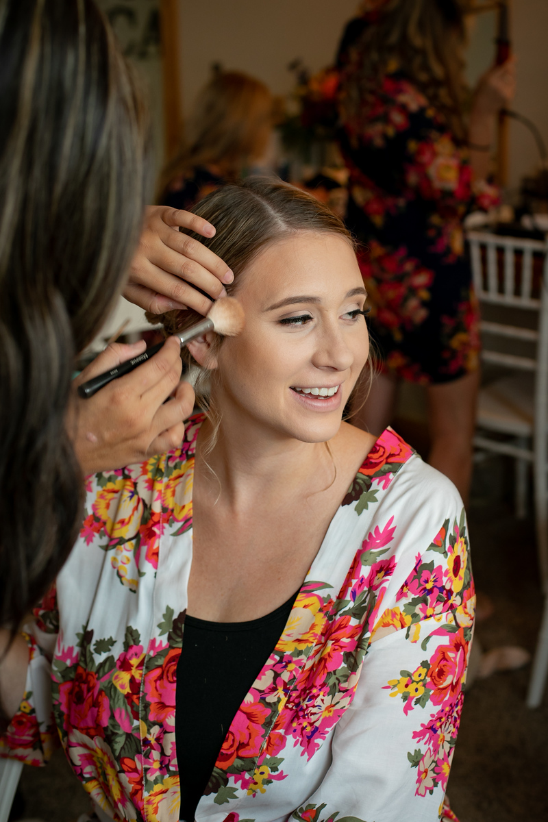 bride wearing a floral robe getting her makeup professionally done on her wedding day