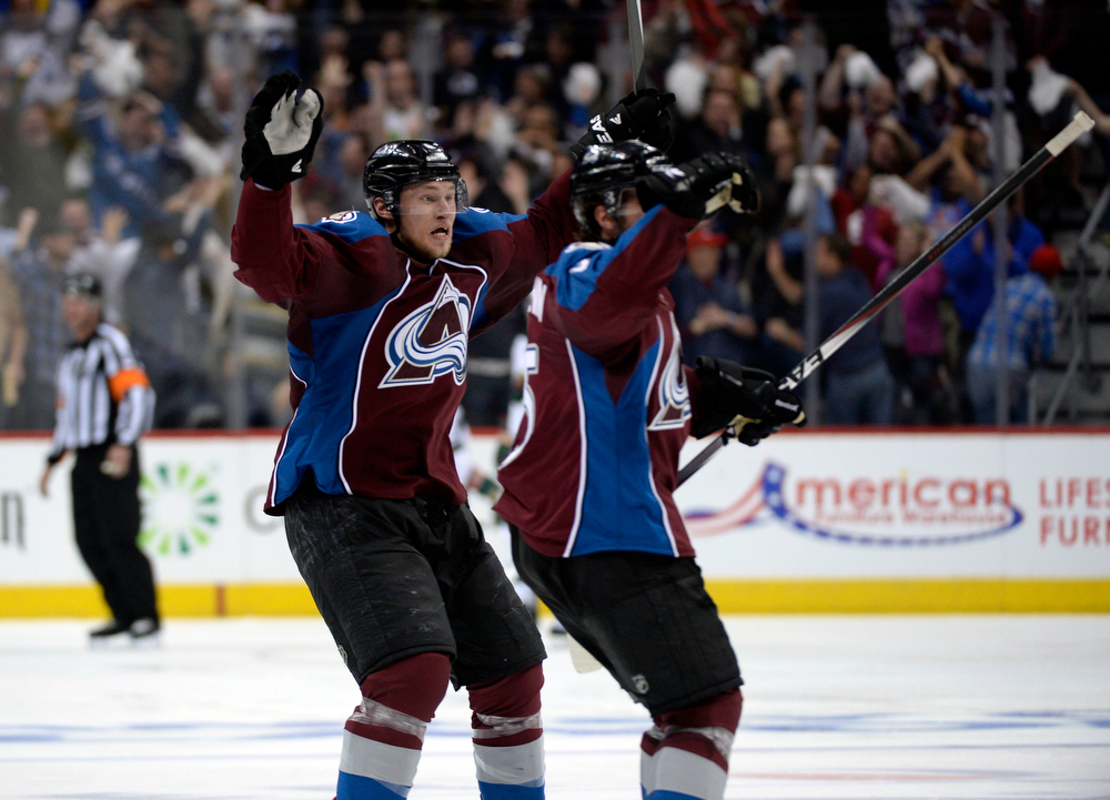 . Erik Johnson (6) of the Colorado Avalanche and Nate Guenin (5) of the Colorado Avalanche celebrate defeating the Wild 5 to 4. The Colorado Avalanche hosted the Minnesota Wild for the first playoff game at the Pepsi Center on Thursday, April 17, 2014. (Photo by John Leyba/The Denver Post)