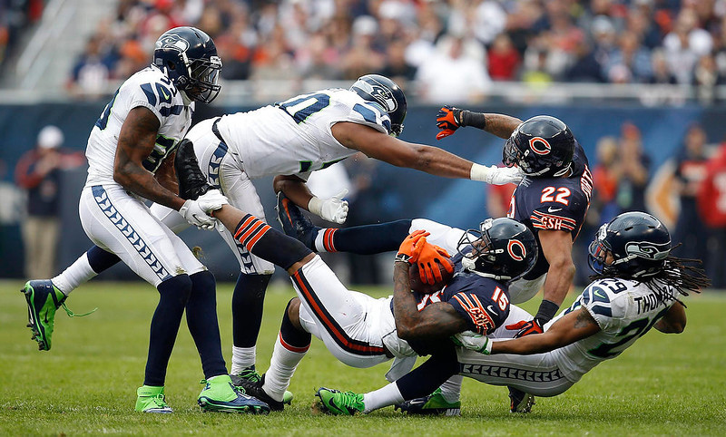 . Chicago Bears wide receiver Brandon Marshall (15) is tackled by Seattle Seahawks cornerback Brandon Browner (39) and free safety Earl Thomas (29) during the first half of their NFL football game at Soldier Field in Chicago December 2, 2012.  REUTERS/Jeff Haynes