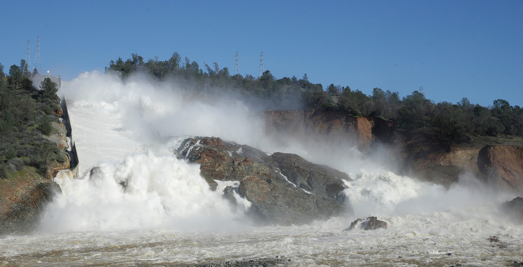 ". In this Saturday, Feb. 11, 2017, water flows down Oroville Dam\'s main spillway, near Oroville, Calif. Officials have ordered residents near the Oroville Dam in Northern California to evacuate the area Sunday, Feb. 12, saying a ""hazardous situation is developing\"" after an emergency spillway severely eroded. (AP Photo/Rich Pedroncelli)"