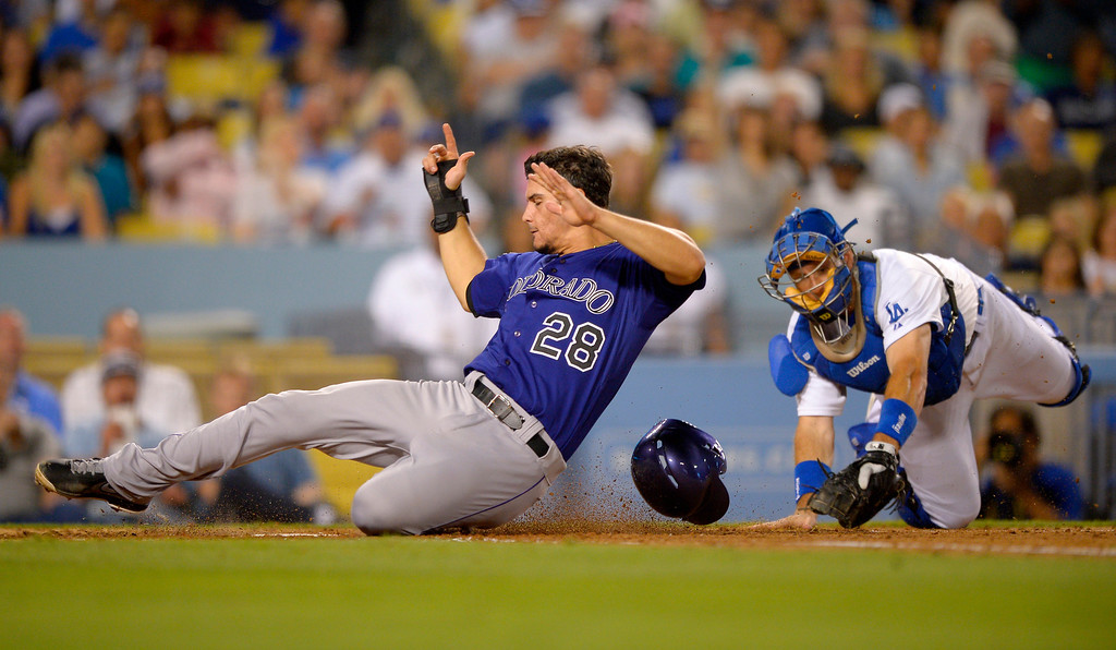 . Colorado Rockies\' Nolan Arenado scores under the tag of Los Angeles Dodgers catcher A.J. Ellis on a single by DJ LeMahieu during the fifth inning of their baseball game, Friday, July 12, 2013, in Los Angeles. (AP Photo/Mark J. Terrill)