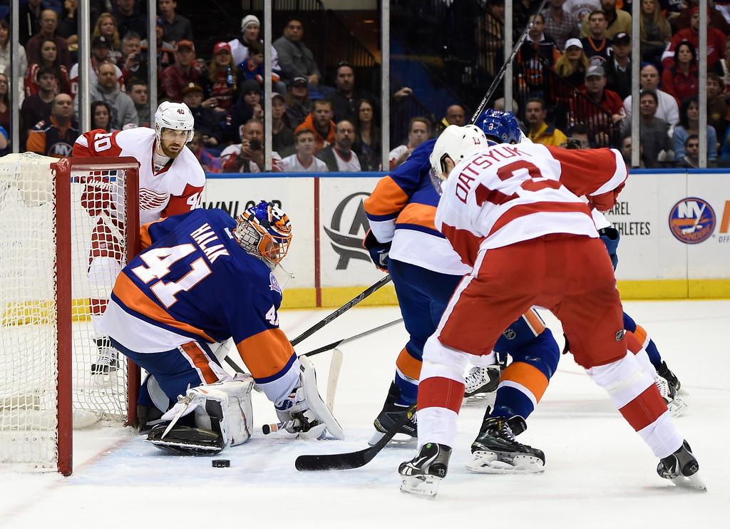 . New York Islanders goalie Jaroslav Halak (41) blocks a shot on goal by Detroit Red Wings center Pavel Datsyuk (13) as Red Wings left wing Henrik Zetterberg (40) waits for the rebound in the third period of an NHL hockey game on Sunday, March 29, 2015, in Uniondale, N.Y. The Islanders won 5-4. (AP Photo/Kathy Kmonicek)