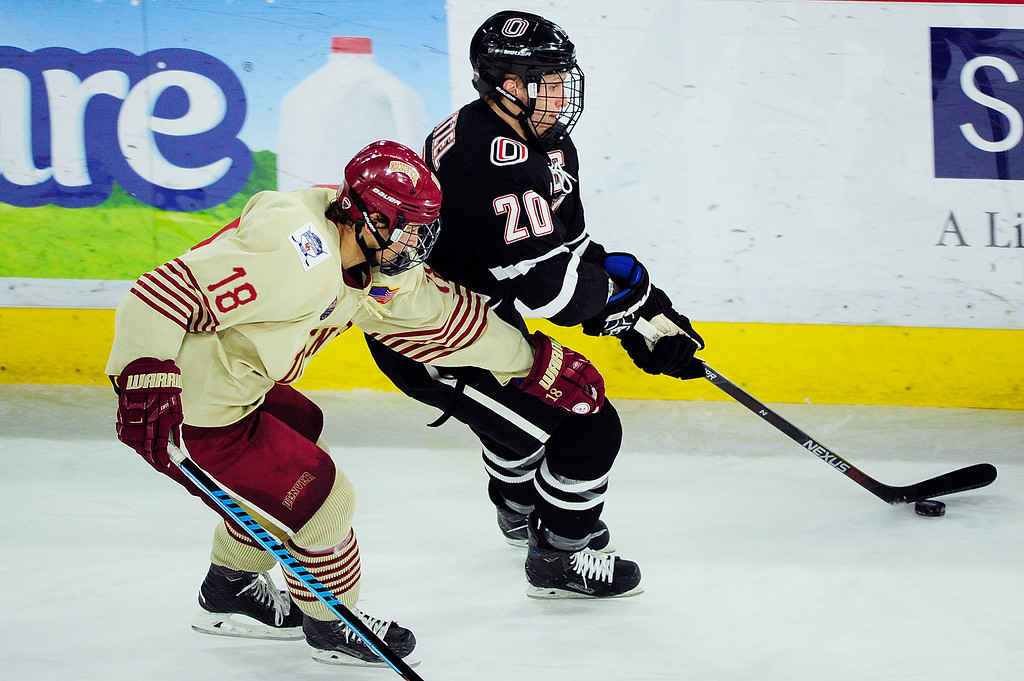 . Denver Pioneers forward Emil Romig (18) tries to strip the puck from Nebraska-Omaha Mavericks forward Jake Guentzel (20) during the third period at Magness Arena on March 4, 2016 in Denver, Colorado. Denver defeated Nebraska-Omaha 3-0. (Photo by Brent Lewis/The Denver Post)