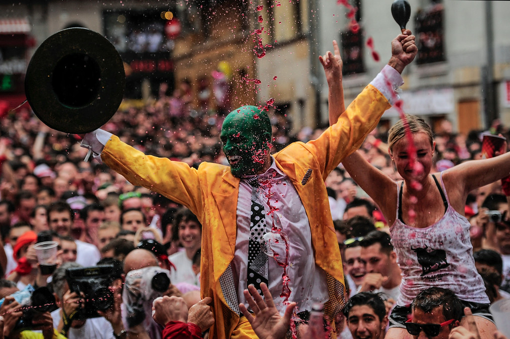 """. Revelers celebrate during the launch of the \'Chupinazo\' rocket, to celebrate the official opening of the 2014 San Fermin fiestas, in Pamplona, Spain, Sunday, July 6, 2014. Revelers from around the world kick off the festival with a messy party in the Pamplona town square, one day before the first of eight days of the running of the bulls glorified by Ernest Hemingway\'s 1926 novel \""""The Sun Also Rises.\"""" (AP Photo/Alvaro Barrientos)"""