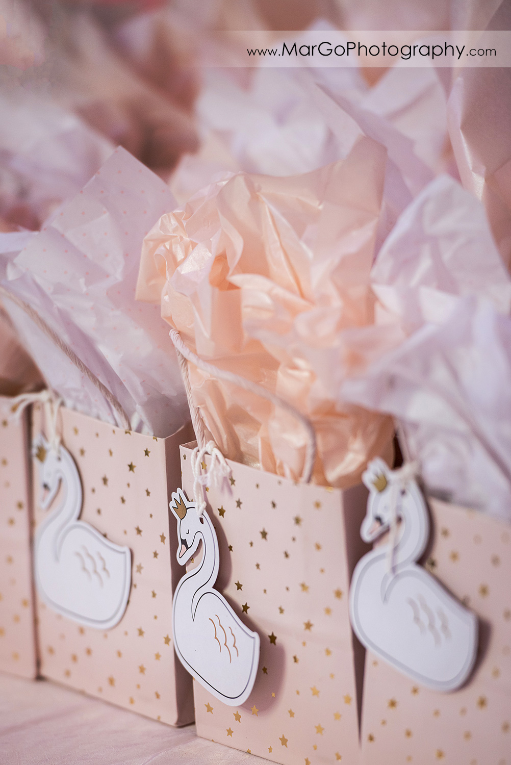 pink party favor bags decorated with white swans and gold stars at Newark Oasis Palace